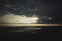 An aerial view of the clouds breaking and the sun rising in a valley