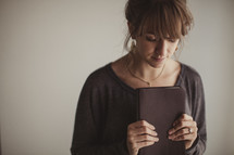 Woman praying as she holds her Bible