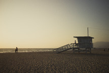 A lifeguard station on a sandy beach at sunset