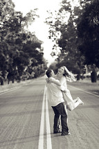 Happy couple outdoors man twirling girl spinning standing in road joy engagement