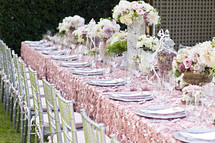 place setting on a set long table at a wedding reception, decor party event, silver chairs, pink linens flatware florals