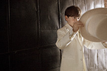 A little boy in a white suit putting on a hat