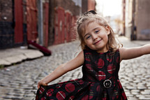 girl child in dress on a cobblestone street