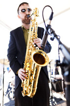 A musician playing a tenor saxophone.