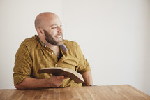 man smiling to the side reflecting while reading a Bible