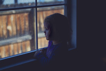 toddler girl looking out a window