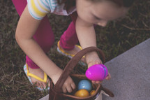 girl putting Easter eggs in an Easter basket