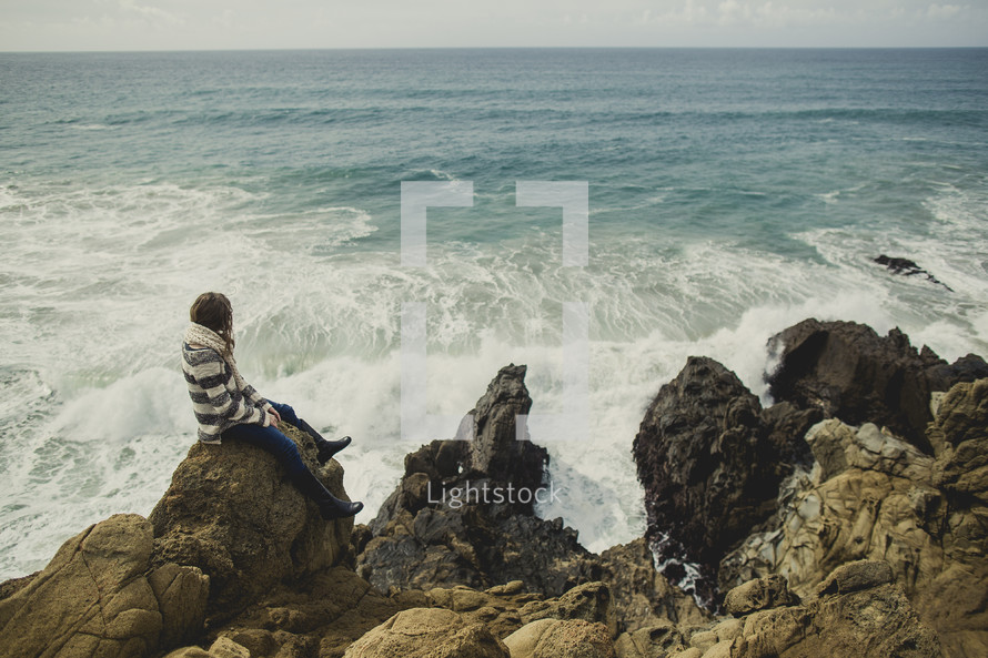Woman sitting on rocky cliff along the ocean.