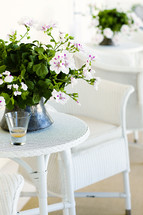 White wicker table chair with geranium centerpieces outdoor porch patio
