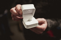 Man holding engagement ring in a box