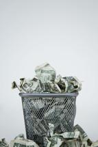 crumpled dollar bills in a trash can