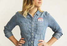 "A young woman in a denim shirt with a button reading, ""I Voted."""