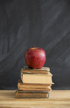 apple on a stack of books in a classroom