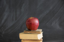 an apple on a stack of books and blackboard