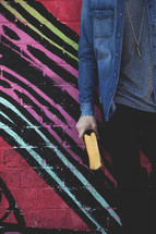 a man holding a Bible at his side in front of a geometric pattern wall