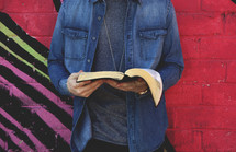 a teen reading a Bible in front of a brightly colored wall