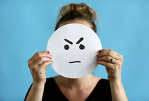 a woman holding up an angry face sign