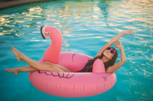a woman relaxing in a flamingo pool float