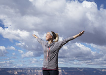 a woman standing at the top of a canyon with open arms