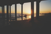 a surfer walking under a pier