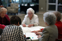 Seniors playing dominoes at a round table.