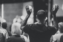 man standing with hands raised in church