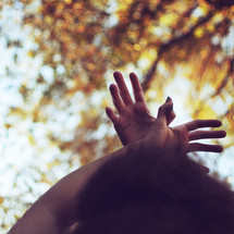 Woman's arms raised in the air with hands to the sky outside.