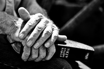 Elderly man's hands holding a Bible.