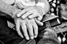Elderly man's hands holding a Bible on his lap.