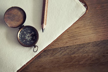 A pencil and compass lying on blank sheets of white paper.