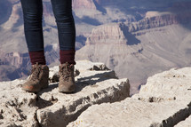 standing at the edge of a canyon cliff