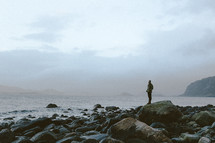 a man standing on a rocky shore in winter