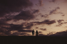 A silhouette of a couple holding hands looking at a cloudy sunset