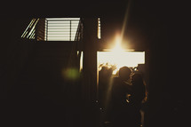 a couple standing in a doorway under the glow of a sunburst