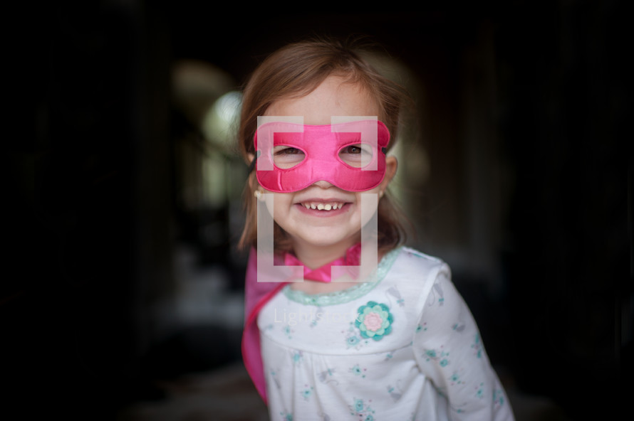 a girl child in a cape and mask
