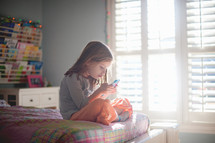 a child sitting on a her bed playing with new apps on a cellphone