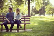 a couple sitting on a park bench looking away from each other