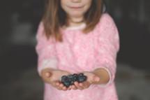 girl child holding blueberries