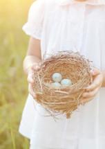 girl child holding a bird's nest