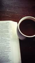 an open Bible and coffee mug