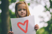A child holding a sign  with a drawing of a heart.