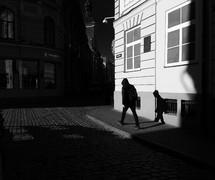 shadow of a man walking on a sidewalk beside of a cobble stone street