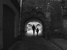 father and son walking holding hands on a cobblestone street