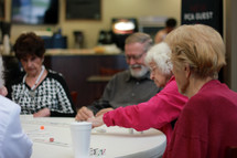 Senior friends playing dominoes at a round table.