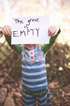 """girl holding a sign that says """"The grave is empty"""""""