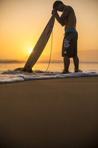 man with his head bowed in prayer over his surfboard