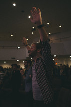 A man with hands raised in worship to God at a worship service.