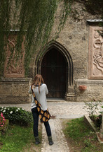 woman taking a picture of an arched wooden door
