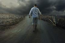 a man walking alone down a dirt road