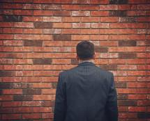 a businessman facing a brick wall